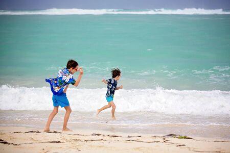 Foto für Adorable preschool children, boys, having fun on ocean beach. Excited children playing with waves, swimming, splashing happily, enjoying family vacation in Mauritius - Lizenzfreies Bild