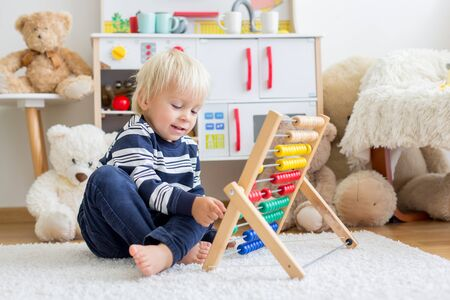 Photo pour Cute toddler boy, playing with counter, colorful abacus, child learning counting alone at home - image libre de droit