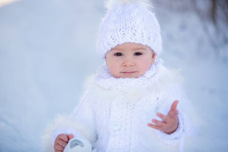 Photo pour Baby playing with teddy in the snow, winter time. Little toddler boy in handmade white snowsuit, holding teddy bear on sunset, playing outdoors in winter park. Children play in snowy park - image libre de droit