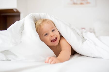 Photo pour Cute little baby boy, relaxing in bed after bath, smiling happily, daytime - image libre de droit