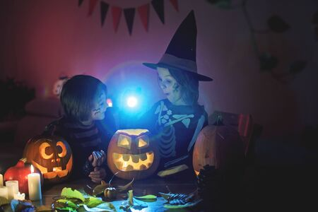 Photo pour Children, boy brothers, playing with carved pumpkin at home on Halloween, making magic potion - image libre de droit