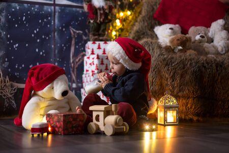 Foto de Boy playing with wooden train at home at night on Christmas night - Imagen libre de derechos