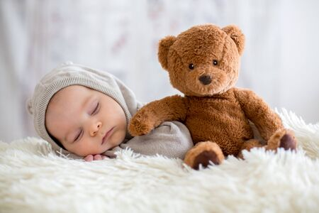 Photo for Sweet baby boy in bear overall, sleeping in bed with teddy bear stuffed toys, winter landscape behind him - Royalty Free Image