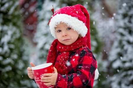Photo pour Sweet beautiful toddler boy, holding cup with hot milk, drinking outdoor in the snow, enjoying winter and Christmas holidays - image libre de droit