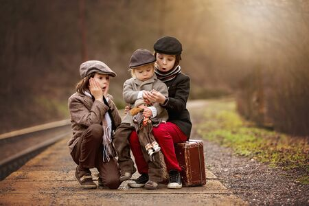 Photo pour Adorable boys on a railway station, waiting for the train with suitcase and beautiful vintage porcelain doll - image libre de droit
