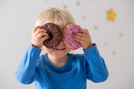 Photo pour Cute sweet blonde child, playing and eating donuts at home - image libre de droit