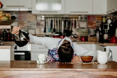Photo pour Tired mother, trying to pour coffee in the morning. Woman lying on kitchen table after sleepless night, trying to drink coffee - image libre de droit
