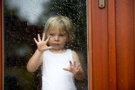 Photo pour Sad child behind the window on a rainy day - image libre de droit