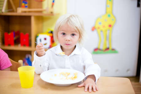 Photo pour Blond toddler child, eating breakfast in kindergarden - image libre de droit