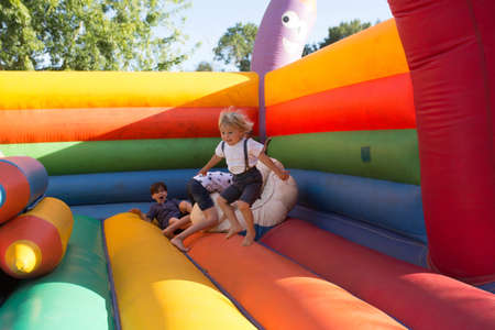 Photo for Children, boys, playing jumping on colorful trampoline in park - Royalty Free Image