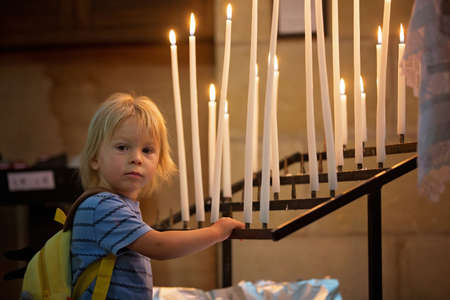 Photo for Little toddler boy, praying in chapel with candles in front of him - Royalty Free Image