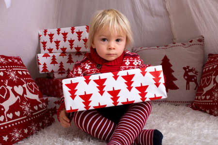 Photo for Cute little blonde boy with Christmas sweater, opening presents at home on Christmas - Royalty Free Image