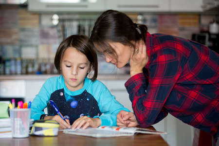 Photo pour Mother, helping her child with homeworks, kid learning at home during pandemic Covid 19 lockdown - image libre de droit