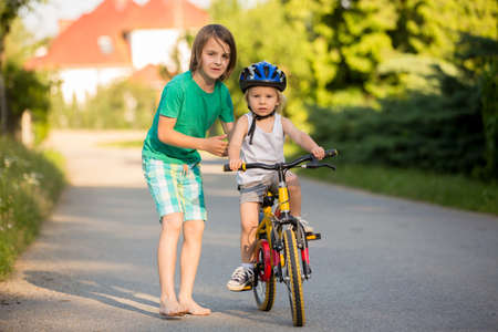 Photo pour Older brother, helping his little brother to learn how to ride a bike, holding him and teaching him biking - image libre de droit
