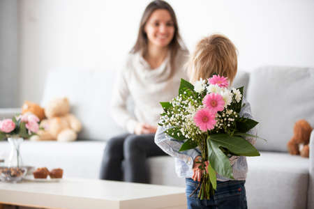 Photo pour Beautiful blond boy, giving mother flowers and box with little gift for mothers day at sunny living room - image libre de droit