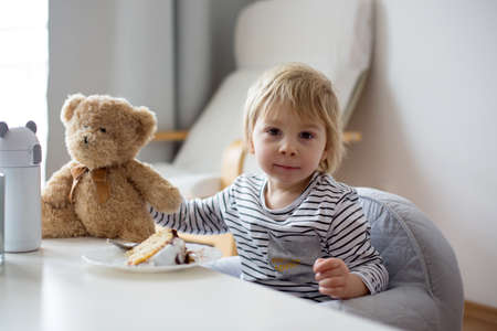 Photo pour Cute toddler child, eating piece of cake and drinking juice at home - image libre de droit