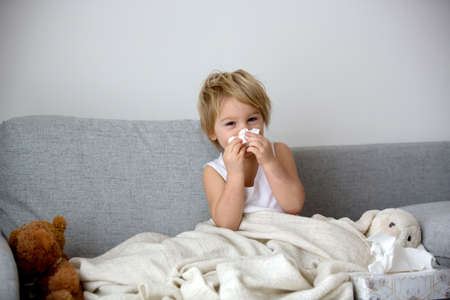 Foto de Blond toddler child, wiping his nose in a tissue, sneezing and coughing at home on a sofa - Imagen libre de derechos