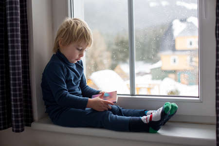 Photo pour Toddler child, sitting on the window, watching the snow falling, reading little book - image libre de droit