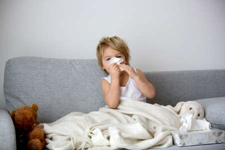 Photo for Blond toddler child, wiping his nose in a tissue, sneezing and coughing at home on a sofa - Royalty Free Image