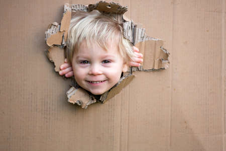 Photo pour Sweet toddler child, cute blond boy, hiding in cardboard box, looking out from a hole, smiling - image libre de droit