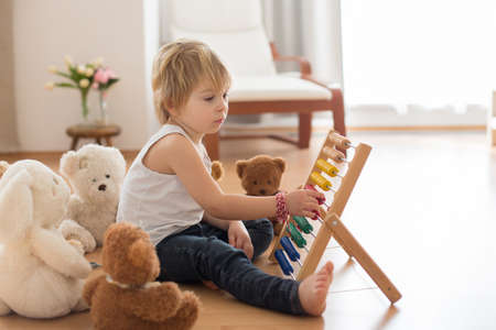 Photo pour Sweet blond preschool child, toddler boy, playing with abacus at home, surrounded by stuffed teddy bears - image libre de droit