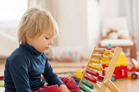 Photo pour Sweet blond preschool child, toddler boy, playing with abacus at home, construction on the floor behing him - image libre de droit