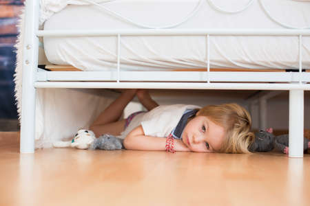 Photo pour Little toddler child, hiding under the bed with stuffed toys, scared from nightmare monsters - image libre de droit