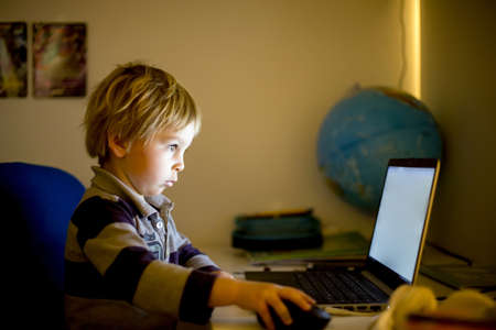 Foto per Sweet toddler boy, playing on notebook at night at home - Immagine Royalty Free