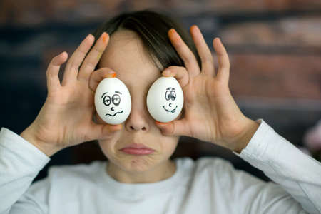 Photo for Cute child, holding white eggs with emotions drawn on them for Easter, funny faces - Royalty Free Image
