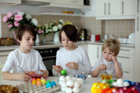 Photo for Children, boy siblings, coloring eggs for Easter at home - Royalty Free Image