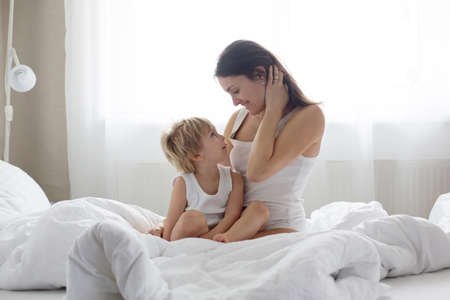 Photo pour Beautiful blond child and his mother, playing at home in the morning in bed, smiling, laughing and having fun together - image libre de droit