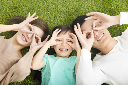 top view of Happy  Young  Family lying on the grass