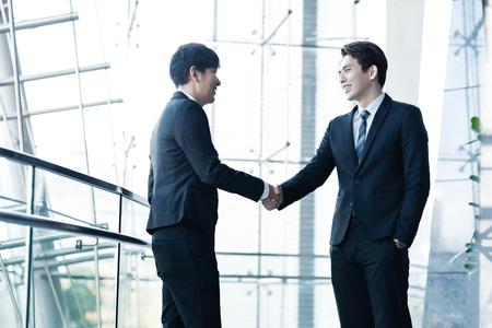 Photo pour Two confident businessmen shaking hands and smiling - image libre de droit