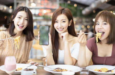 Photo for Happy friends having dinner and showing smart phone in  restaurant - Royalty Free Image