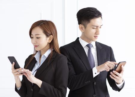 Photo pour Young smiling businesswoman and businessman watching smart phone - image libre de droit