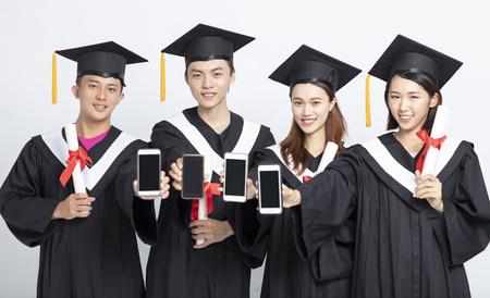 Photo pour Group of graduate students showing smart phone - image libre de droit