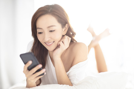 Photo for young smiling woman watching mobile phone on bed - Royalty Free Image