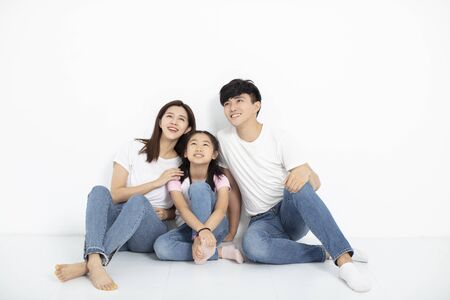 Photo for Happy Young family Sitting On Floor Looking Up - Royalty Free Image