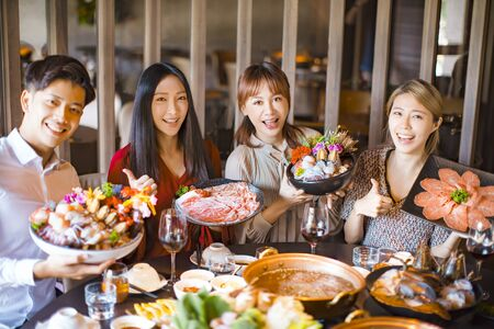 Photo pour young friends showing seafood  beef and pork slices  in hot pot restaurant - image libre de droit