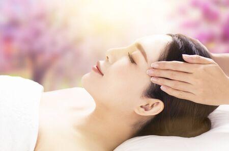 Photo pour closed young woman face and head massage in spa - image libre de droit