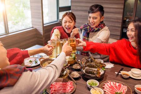 Photo pour happy young group toasting beer at hot pot restaurant - image libre de droit