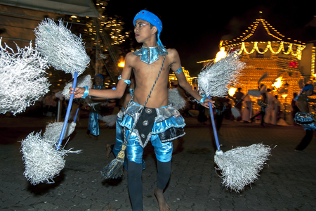 Colourful Chamara Dancers perform a dance whereby the yak tails they hold symbolically fan the Sacred Tooth Relic during the Esala Perahara in Kandy, Sri Lanka. The Esala Perahera runs every year in late July or early August for ten days, ending on the Ni