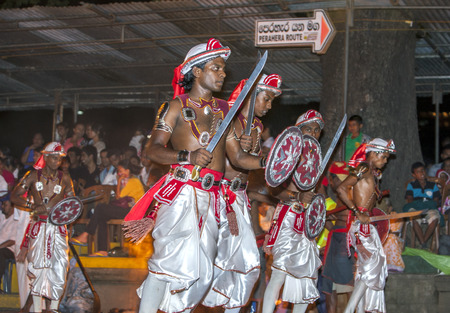 Sword Dancers perform along the streets of Kandy during the Esala Perahera in Sri Lanka. The Esala Perahera festival runs every year in late July or early August for ten days, ending on the Nikini poya full moon and is held to honour the Sacred Tooth Reli