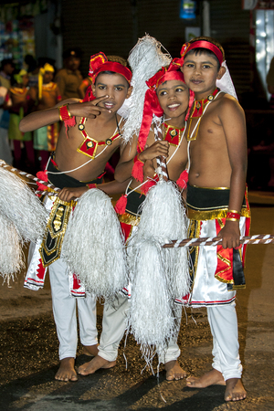Young Chamara Dancers wait for the Esala Perahera to begin in Kandy in Sri Lanka. Chamara Dancers perform a dance whereby the yak tails they hold symbolically fan the Sacred Tooth Relic. The Esala Perahera (great procession) is held to honour the Sacred T