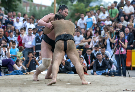 Japanese sumo wrestlers engage in battle during an exhibition bout in Edirne in Turkey. A large crowd of Turkish people are gathered to watch the exhibition.