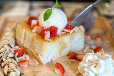 Photo for Strawberry honey toast with ice cream on the wood plate dish. - Royalty Free Image