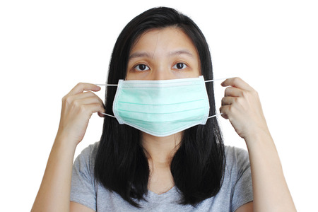 Photo for Portrait of Asian woman putting on medical mask on white background. - Royalty Free Image