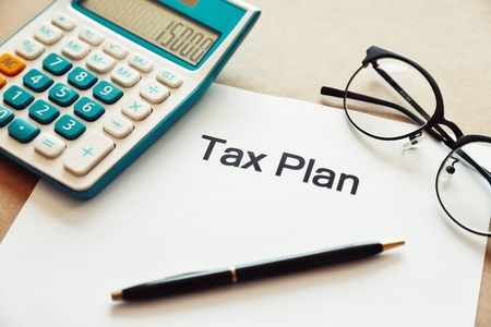 Photo pour Close up tax planning word on paper with calculator, pen and eye glasses place on the wooden table. - image libre de droit