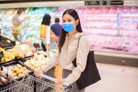 Foto für woman is shopping in supermarket with face mask - Lizenzfreies Bild