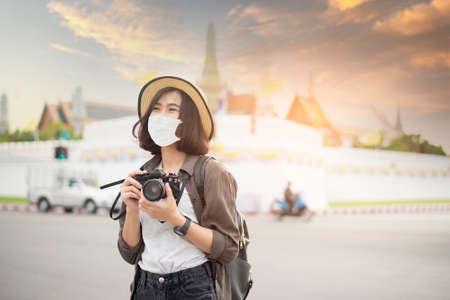 Photo pour A young pretty Asian woman is wearing protective mask travelling around famous places in Bangkok city , New normal travel, covid-19 protection , safe travels , travel under COVID-19, Post- pandemic travel concept. - image libre de droit